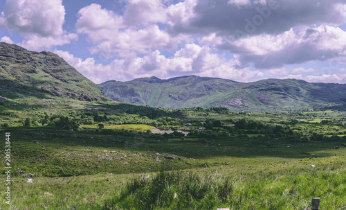 Fotobehang Purper The green fields and mountains as seen from Healy Pass, a 12 km route worth of hairpin turns winding through the borderlands of County Cork and County Kerry in Ireland