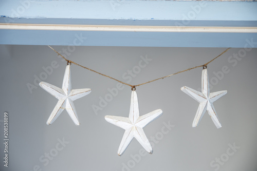Three small wooden white stars hanging over the door. Wallpaper Mural