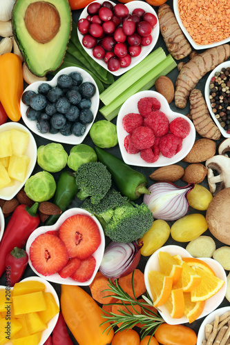 In de dag Assortiment Healthy super food concept with fruit, vegetables, herbs spice and nuts in heart shaped dishes and loose. Foods high in antioxidants, omega 3 fatty acids, fibre,vitamins, minerals and anthocyanins.