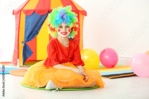 Cute little girl with clown makeup in carnival costume indoors. April fool's day celebration