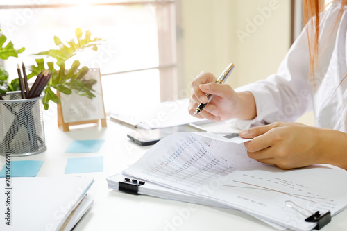 Close up audit woman calculate on paper document financial data. Canvas Print
