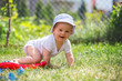 Little baby boy, playing with big construction blocks in garden