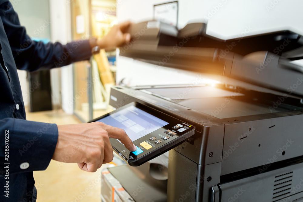 Fototapeta Bussiness man Hand press button on panel of printer, printer scanner laser office copy machine supplies start concept.