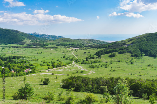 Staande foto Pistache A beautiful landscape view over a mountain valley and forested mountain peaks of Velebit mountain range in Croatia of the Adriatic sea or coastline with islands. Summer in Croatia or travel concept