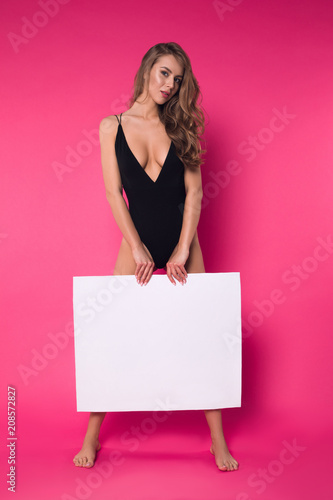 Poster Akt Beauty comes when fashion succeeds! Full length photo of the young attractive girl posing in the black lingerie on the isolated pink background.