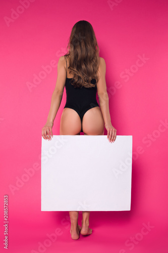 Poster Akt Create your own style! Trendy good-looking lady in the wonderful fit in sexy lingerie standing with her back to the camera, while posing for photo with blank board.