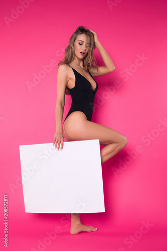 Poster Akt Style is eternal! Full length picture of the young stylish well-graced girl posing on the isolated pink background with white board.