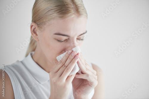 Valokuva  Rhinitis. Girl with napkin on white background