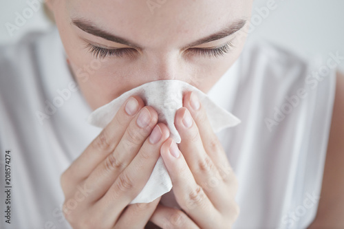 Fényképezés  Rhinitis. Girl with napkin on white background