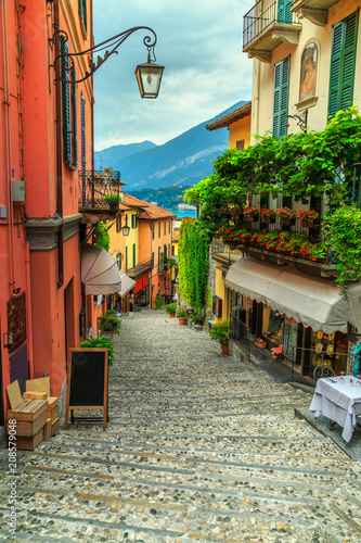 Stunning scenic street with colorful houses and flowers in Bellagio
