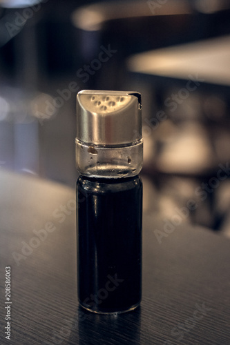Jar with soy sauce on a wooden table