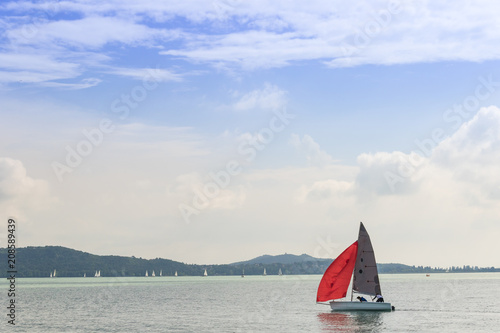 Foto op Canvas Zeilen Boat with a red sail sailing on the lake under the blue cloudy sky on a sunny day