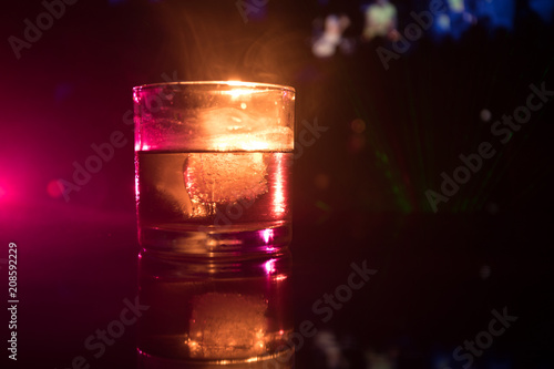 Poster Bar selective focus pure whisky with ice cube inside whisky glass on dark foggy background alcohol drink concept.