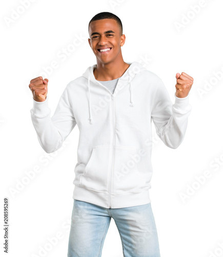 Fotomural  Dark-skinned young man with white sweatshirt celebrating a victory and happy for