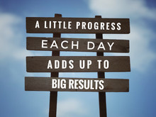 Motivational And Inspirational Quote - 'A Little Progress Each Day Adds Up To Big Results' On Plank Signage. With Vintage Styled Background.