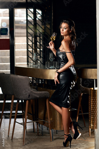 Young Beautiful Woman In Sexy Short Black Leather Dress Having Good
