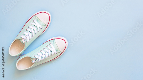 Pastel turquoise female sneakers on blue background. Flat lay, top view minimal background. Fashion blog or magazine concept.