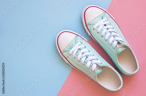 Pastel turquoise female sneakers on blue and pink background. Flat lay, top view minimal background. Fashion blog or magazine concept.