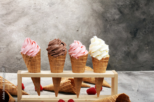 Fototapeta Vanilla frozen yogurt or soft ice cream in waffle cone.