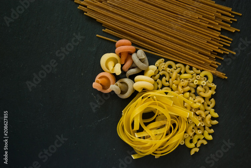 Fotografie, Obraz  variety of italian uncooked pasta flat lay on a black background with copy space