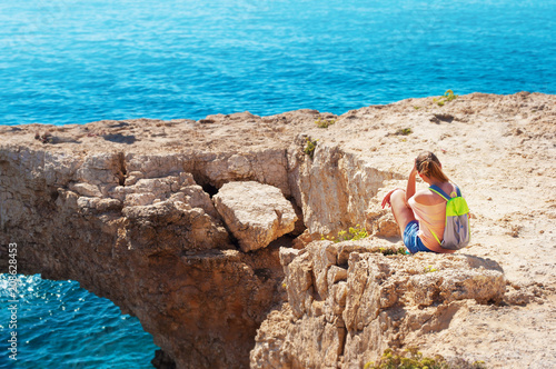 Foto op Plexiglas Cyprus One caucasian girl sitting on the edge of the cliff