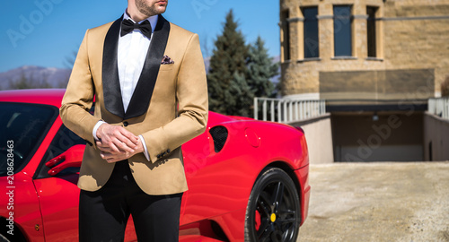Man in custom tailored tuxedo, suit posing outdoors in front of expensive car Wallpaper Mural