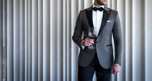 Valokuva Man in custom tailored tuxedo, suit holding glass with wine and posing indoors i