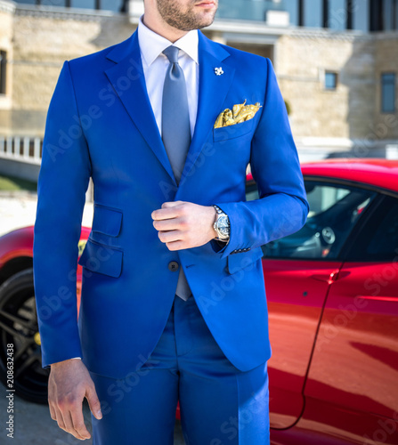 Man in expensive custom tailored suit posing in front of expensive car outdoors Wallpaper Mural