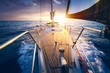 canvas print picture - Sunset at the Sailboat deck while cruising / sailing at opened sea. Yacht with full sails up at the end of windy day. Sailing theme - background. Yachting design.