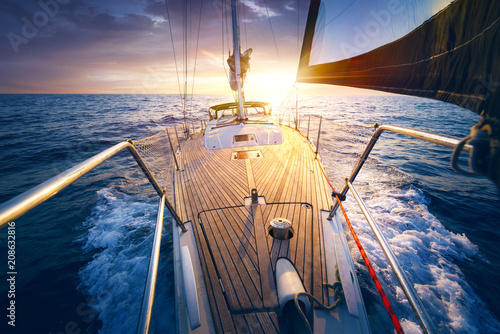 Sunset at the Sailboat deck while cruising / sailing at opened sea. Yacht with full sails up at the end of windy day. Sailing theme - background. Yachting design.
