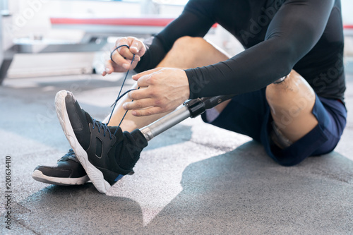 Photo Close-up of man with an amputated leg tying shoelaces on sneakers