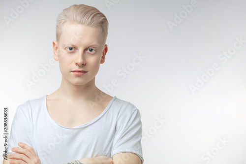 Obraz na plátně  Portrait of blonde young man with uncommon appearance wears white t shirt, looking at camera, isolated over white studio background with copyspace for text
