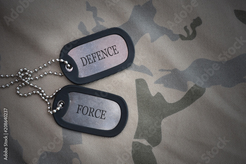 Fotografia  army blank, dog tag with text defence force on the khaki texture background