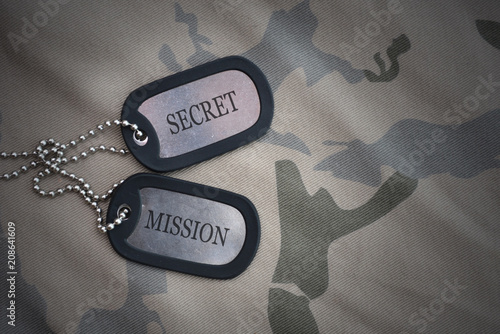Photo  army blank, dog tag with text secret mission on the khaki texture background