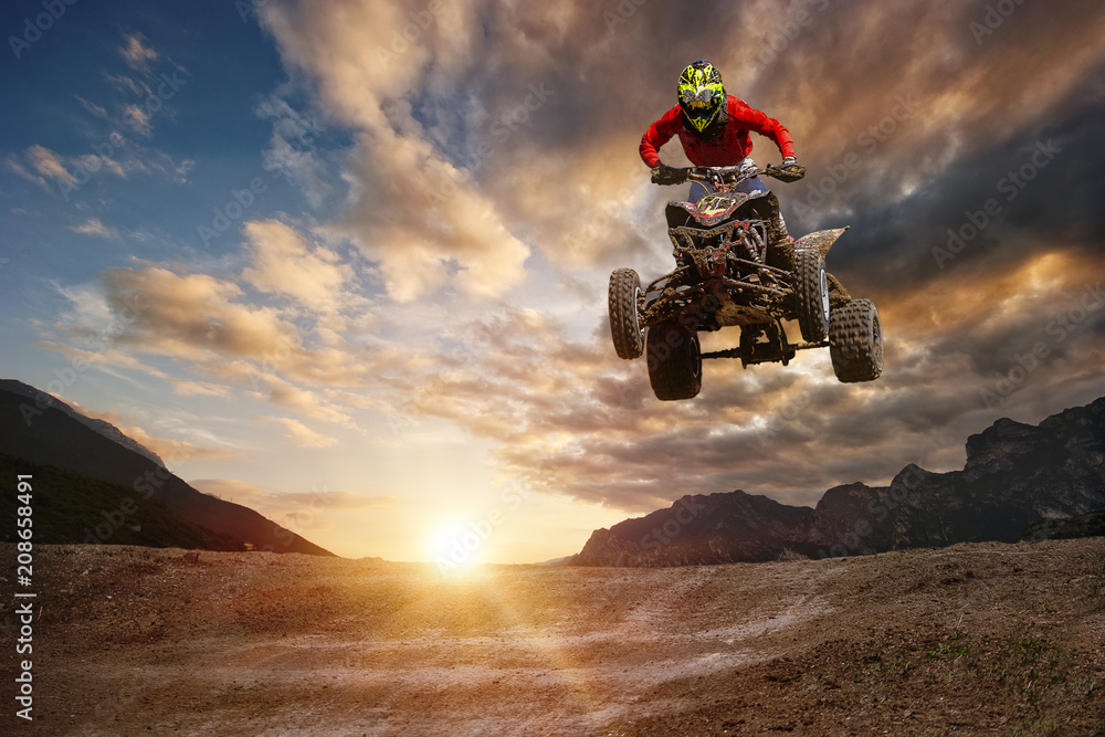 Fototapety, obrazy: Man on atv jump on the trail during sunset.