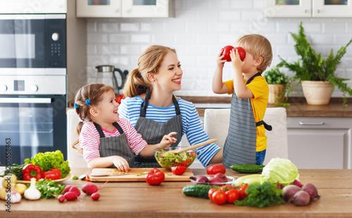 Poster Cuisine mother with children preparing vegetable salad .