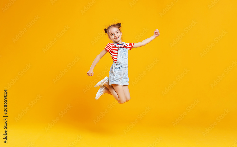 Fototapety, obrazy: funny child girl jumping on colored yellow background