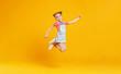 Leinwandbild Motiv funny child girl jumping on colored yellow background