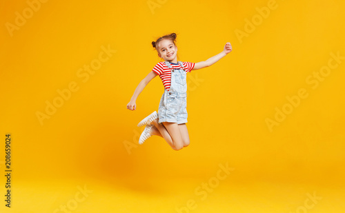 Photo  funny child girl jumping on colored yellow background