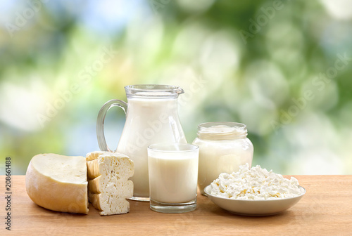 Fotobehang Zuivelproducten Milk, sour cream, cheese and cottage cheese on wooden table on defocused of natural background with space for text