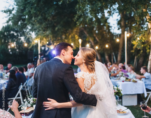 Fototapeta Beautiful newlyweds kiss at a wedding party with lamps. Stylish wedding ceremony. obraz