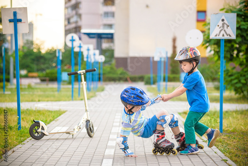 two boys in park, help boy with roller skates to stand up