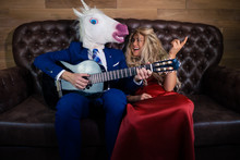 Young Man In Elegant Suit And Comical Mask Playing Music On The Guitar For Pretty Girl In Red Dress. Unusual Couple Spend Time Together On A Leather Sofa In Stylish Apartment. Unicorn With Girlfriend