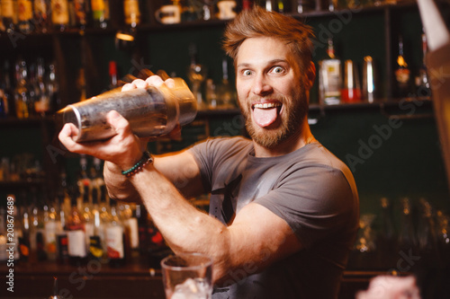 Joyful bartender mixes a cocktail in a shaker Obraz na płótnie