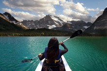 Person Kayaking In Beautiful Blue Lake With Mountain Scenery, Peaceful Travel Adventure
