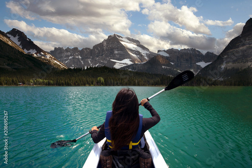 Valokuva  Person kayaking in beautiful blue lake with mountain scenery, peaceful travel ad