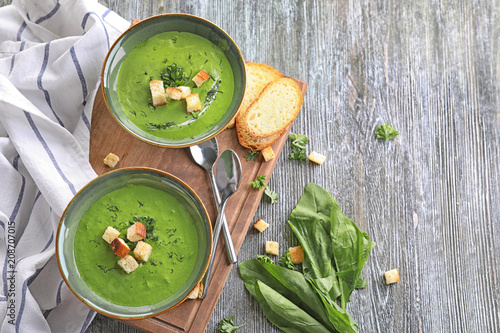 Bowls with delicious spinach soup on wooden board