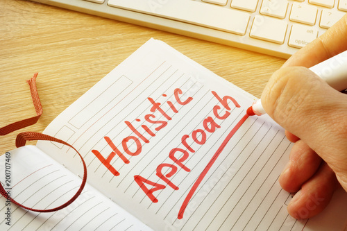 Photo  Hand is writing Holistic approach in the note.