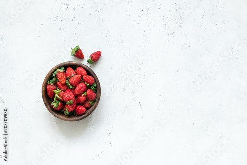 Strawberry in a bowl. Fresh strawberries. Harvest of fresh organic strawberries on white concrete background. Top view with copy space for text