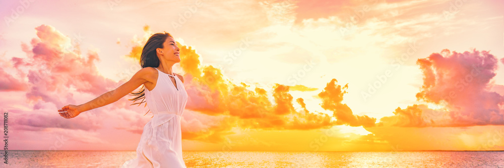 Fototapeta Well being free woman with open arms in the air blissful happiness concept banner. Happy woman against pink pastel colorful sunset sky.